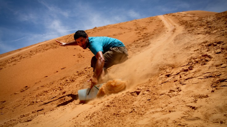 Sandboarding down the sand dunes in the Death Valley