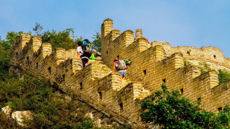 Tourists carrying backpacks hiking up the Great Wall of China