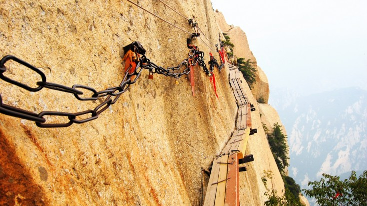 Planks and chains nailed to the side of a rocky mountain