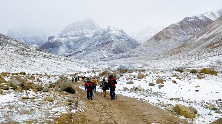 Tourists trekking around the base of a Mountain
