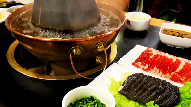 Water boiling in hot pot, vegetables, sauce and slices of meat