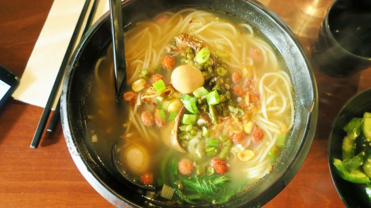 A bowl of soupy noodles with meat and vegetables
