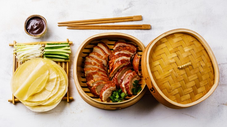 Slices of meat in a wooden container, rolled dough, sauce and chopsticks