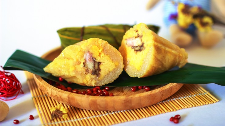 Yellow colored dish made of stuffed rice on bamboo leaves