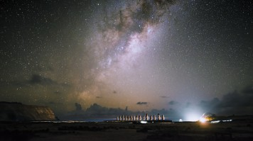 The moai statues stand against the Pacific ocean under the starry nightsky