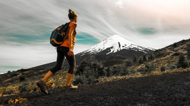 A woman hiking up a trail next to a snow-capped volcano