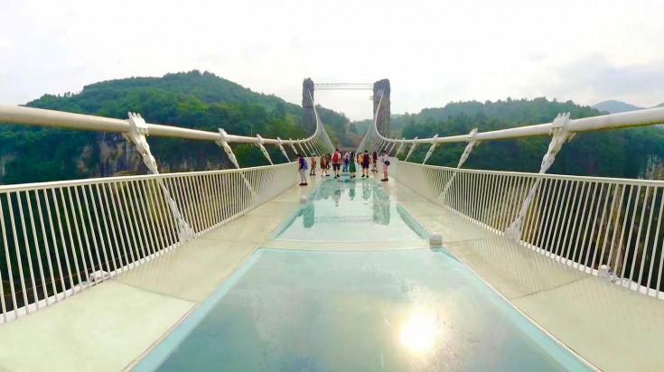 Tourists walking on world's longest glass bridge at Zhangjiajie