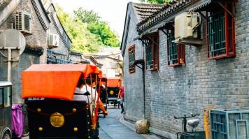 Tourists exploring the Beijing Hutong in traditional rickshaws