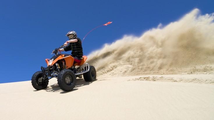 Ride through the sand on a quad bike in a desert safari in Dubai