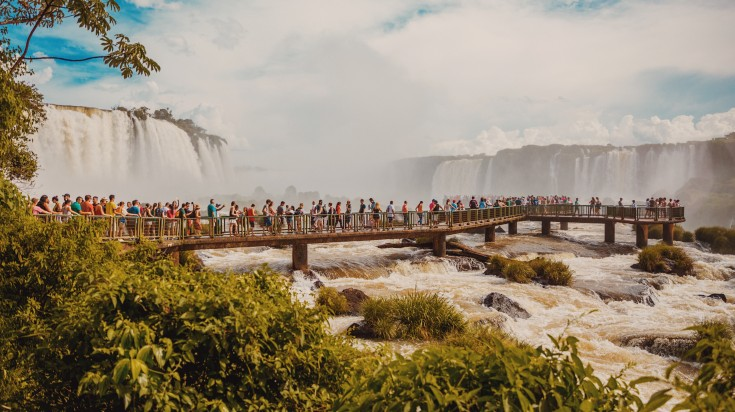 People at a viewing deck built on a river with waterfalls in the background