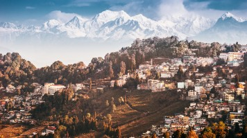 A hill station with snowy mountains behind it