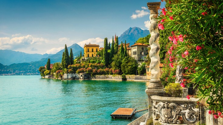 Lake Como has glittering dark blue lake waters that are bordered by the most glorious hills and mountains, and beautiful villages and towns are clustered along the shore.