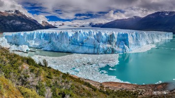 A humongous block of glacier on turquoise lake surrounded