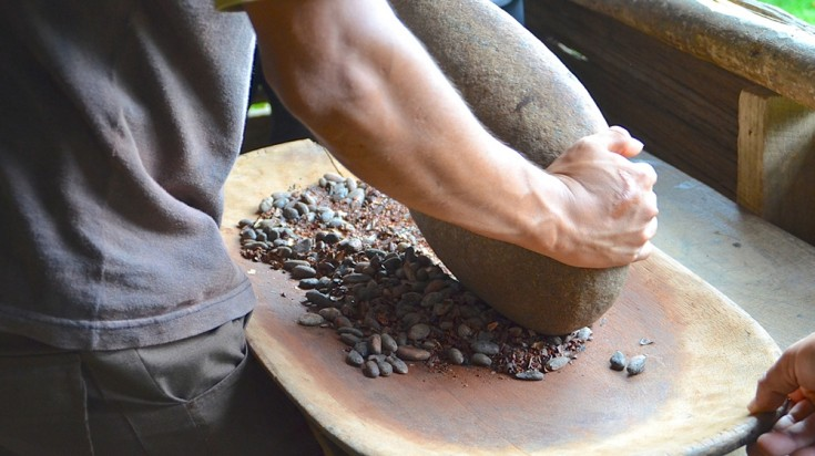 Man grinding cacao beans in Costa Rica