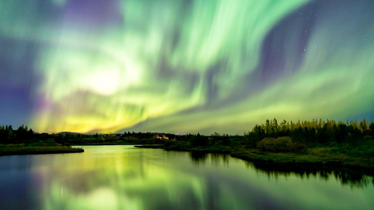 Green and yellow lights in the sky reflecting on the river below
