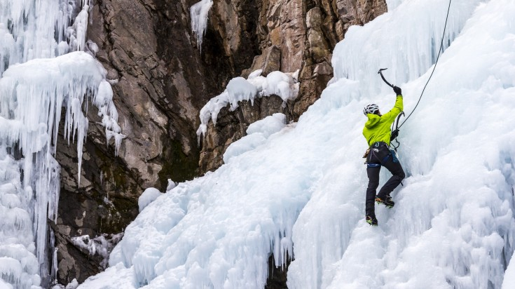 A man wearing climbing gears and harness and climbing icy, rocky mountain