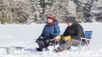 A couple sitting on frozen, snowy lake with fishing rods in hands