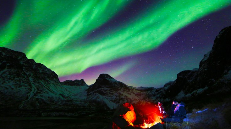 Tourists amidst mountains watching green lights in the night sky