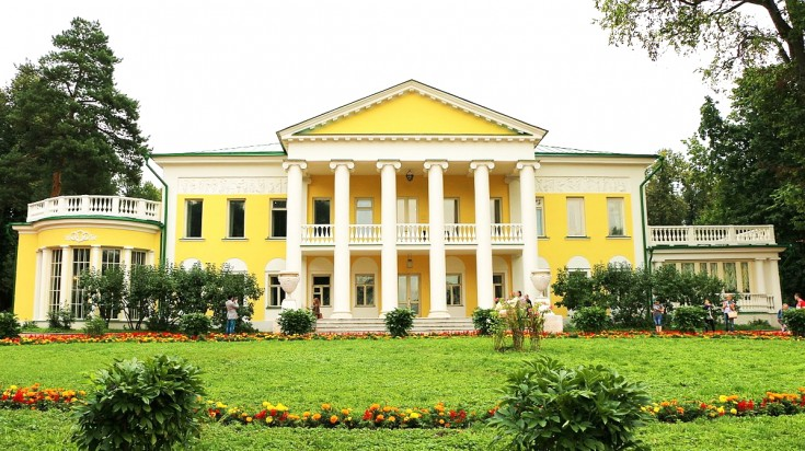 View of a yellow coloured mansion with a garden in front