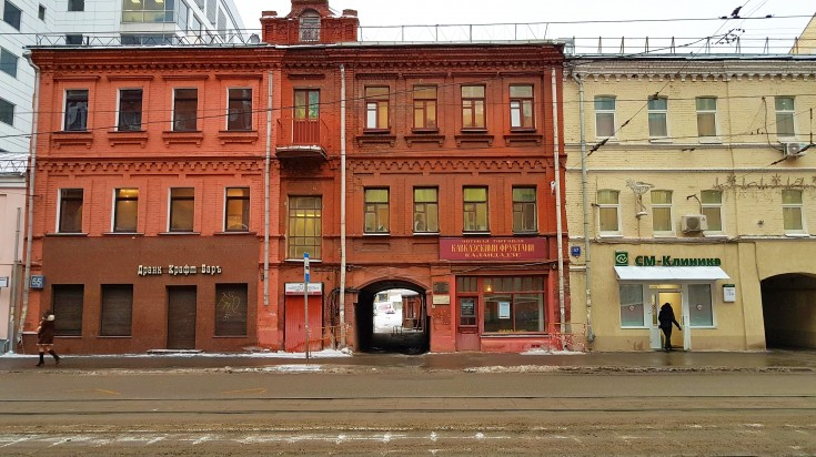View of red and yellow colored buildings from across the street