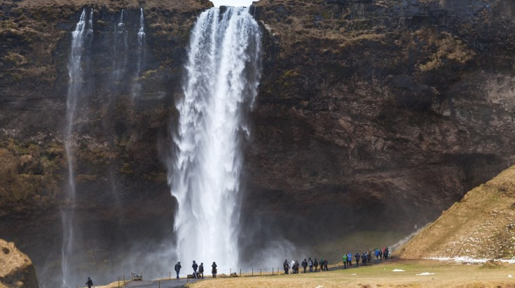 Tourist walk near the giant Seljalandsfoss waterfall