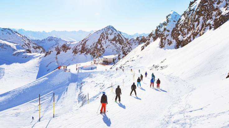 skiers ski down a slope in the France Alps