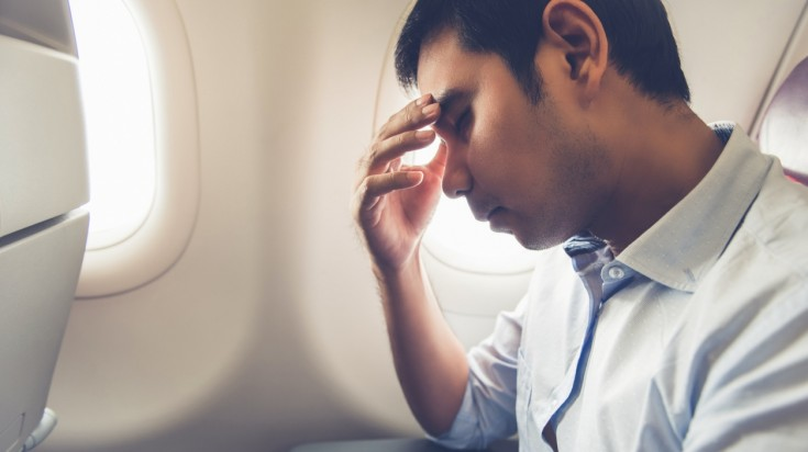 Man trying to sleep on a plane