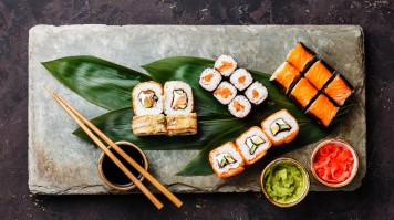 Sushi is prepared with rice and various toppings like salmon and veggies.