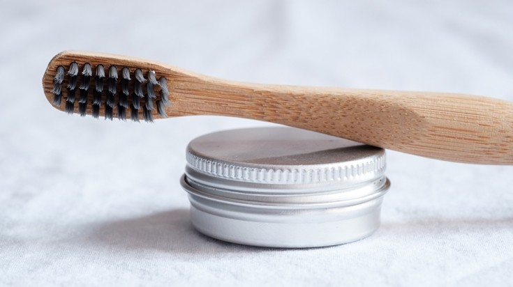 Bamboo toothbrush and tin-boxed shampoo bars for sustainable travel