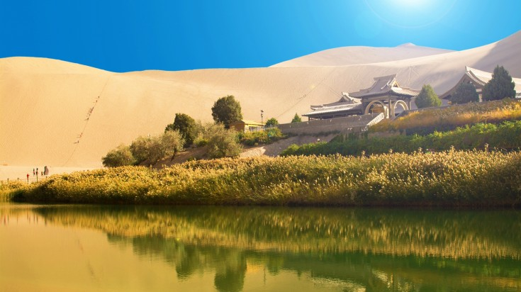 A traditional building surrounded by sandy desert, grasses and a lake