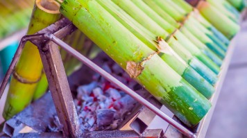 Bamboo stuffed with rice and other ingredients being cooked over coal