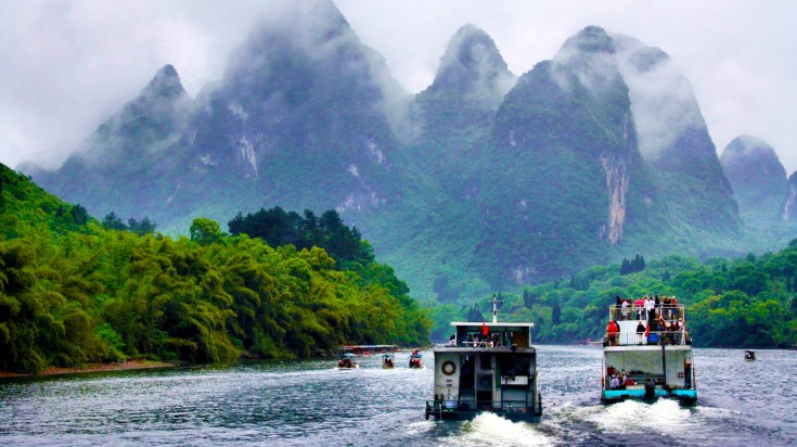 Tourists taking boat rides and cruising towards the hills on Li River