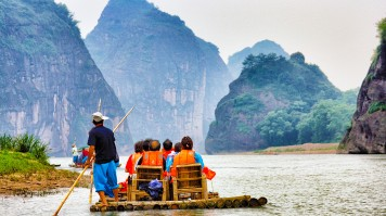 Tourists wearing life jackets on a bamboo raft and cruising downstream
