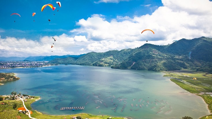 paragliders in the air with a turquoise lake below in Pokhara