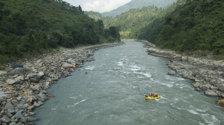 A roaring river runs in between two hills, with a raft afloat in Pokhara