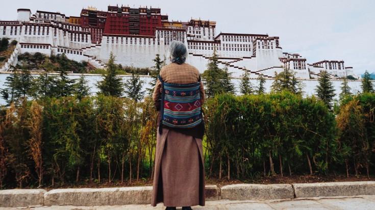 An old Tibetan lady gazes at the Potala Palace