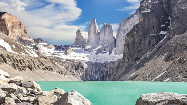 Three towering rock formations against the backdrop of turquoise blue lake