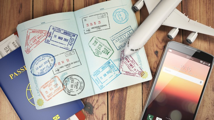 Immigration stamps, a toy airplane and a cellphone signifying travel