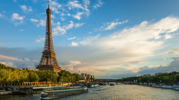 the Eiffel tower stands next to a river in Paris