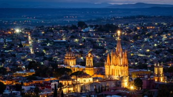 A well lit cathedral and the town at dusk in Mexico