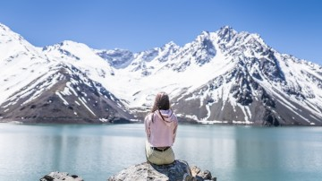 girl sits on a rock overlooking a blue lake and snow-capped mountains