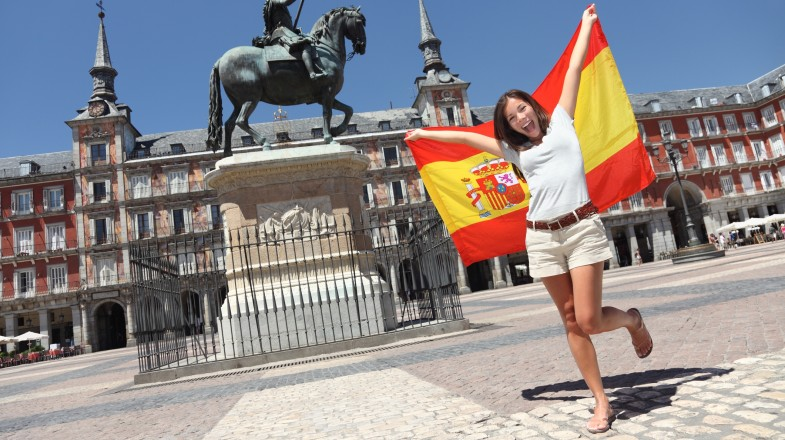 A tourist poses for a picture with the flag of Spain