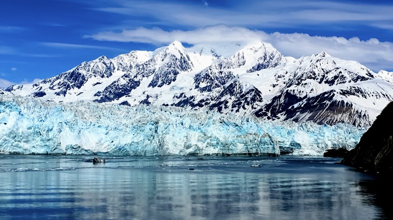 An Alaska cruise ship sailing parallel to glaciers on the frosty ocean