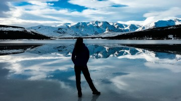 A tourist admires the stunning snowy-mountain scenery during winter in Argentina
