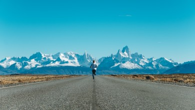 Man running on asphalt road toward snow-covered mountains in the background in Argentinian Patagonia on an Argentina itinerary.