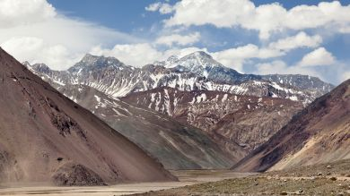 Snow-capped peaks that run down into rugged cliffs form the dramatic backdrop of Cajon del Maipo.