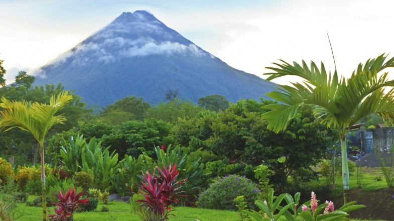 A green park in Costa Rica featuring Arenal Volcano looming in the background