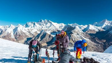 Trekkers enjoying amazing view of snow capped mountains.