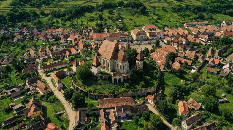 Aerial view of a church surrounded by a village in Transylvania