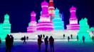 Tourists amidst illuminated sculptures at the Harbin Ice Festival at night
